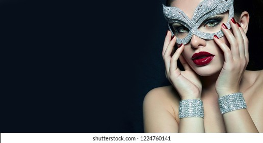 Portrait of a beautiful attractive girl with a red lipstick in a diamond mask and diamond bracelets. Jewelry.fashion, beauty, makeup, cosmetics, beauty salon, style, personal care, posture.