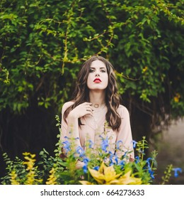 Portrait of a beautiful attractive lady of a young slender brunette girl with long dress walking through a green park with flowers at sunset lifestyle outdoor