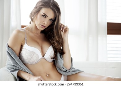 Portrait of a beautiful attractive and sexy young adult sensuality pretty brunette woman in white lingerie and grey sweater on the white couch in sunlight window on luxury apartment