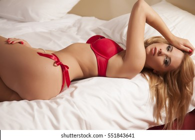 Portrait of a beautiful attractive and sexy young adult sensuality pretty blonde woman in red lingerie on the bed in bedroom luxury apartment