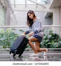 Portrait of a beautiful, attractive and young Indian Asian girl unzipping her bag to find something in her luggage or to repack her items before check in at the airport during the day.