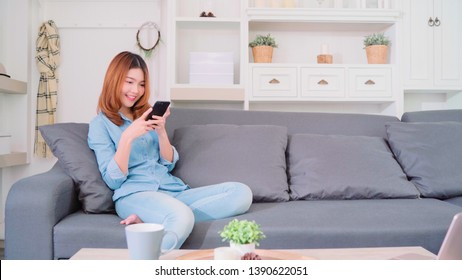 Portrait of beautiful attractive young smiling Asian woman using smartphone while lying on the sofa when relax in living room at home. Enjoying time lifestyle women at home concept.