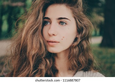 Portrait of a beautiful authentic curly-haired girl in the park in a light beige sweater with blue eyes and birthmarks on her face. No makeup.