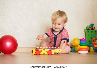 Portrait of a beautiful baby boy on the floor with music toys. 1,5 year-old child playing with educational cup toys at home. Little blond kid with blue eyes is playing with toy at home indoors