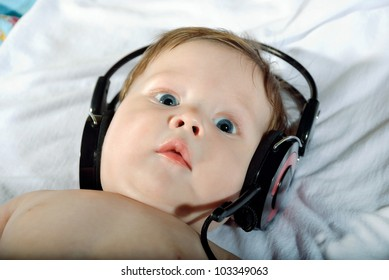 Portrait of a beautiful baby with headphones listening to music.