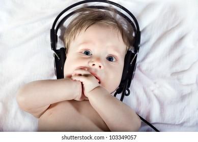 Portrait of beautiful baby listening to music on headphones.