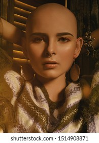 Portrait of a beautiful bald girl on a dark background. model in round earrings and a striped poncho