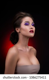 Portrait of a beautiful big breasted asian girl wearing deep decollete and aggressive red lips makeup. Red and black background. Smooth healthy skin. Copy space. Commercial and advertisement design.