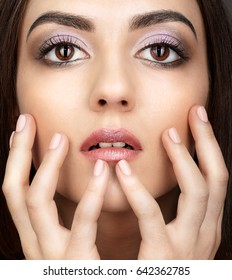 Portrait of beautiful big-eyed young brunette woman  with hands near face