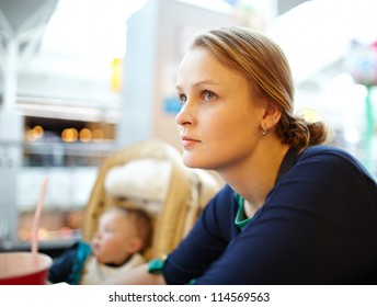 Portrait of a beautiful a bit tired girl having rest in the supermarket. Shallow dof, nice warm colors, natural sunlight through the windows.