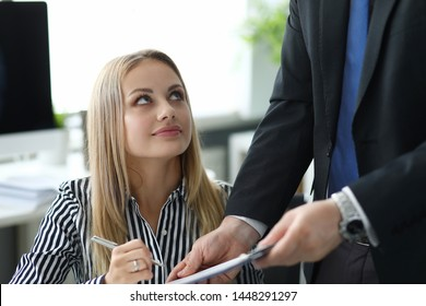 Portrait of beautiful biz woman underwriting important profitable agreement. Colleague looking up at partner with gladness. Business concept. Blurred background