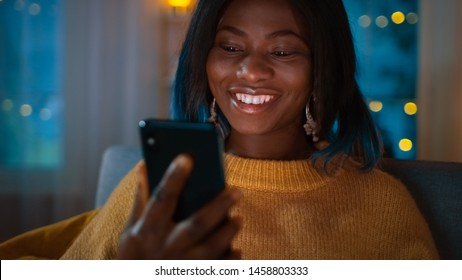Portrait of Beautiful Black Girl Uses Smartphone while Sitting on a Couch at Home, Her Face is Illuminated with a Screen Light. In the Cute Woman Smiles and Browses Through Internet.