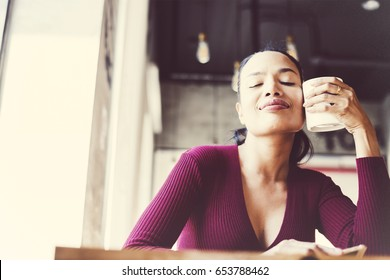 Portrait of beautiful black hair Business woman with a cup coffee and closing eyes with beautiful smile  after work in coffee shop.Love concept.