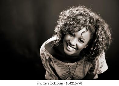 Portrait of beautiful black woman on black background. Studio shot