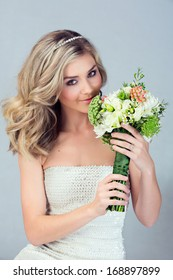 Portrait of a beautiful blond bride with a diamante headpiece. Hair in loose curly style. Wearing sequin modern dress
