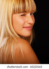 portrait of beautiful blond girl looking above her shoulder and winking