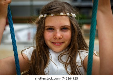 Portrait of a beautiful blond girl on a swing with a small wreath of white flowers on her head, on her communion day