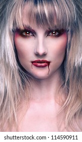 portrait of a beautiful blond girl vaprire with bloody streaks