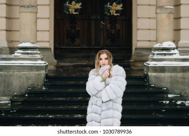 portrait of a beautiful blond girl who stands on the street near the steps and looks at the camera