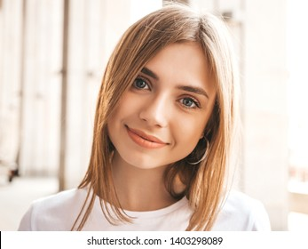Portrait of beautiful blond model dressed in summer hipster clothes. Trendy girl posing in the street background. Funny and positive woman having fun
