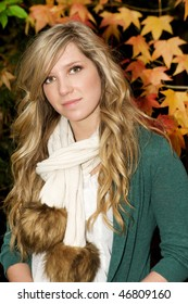 Portrait of a beautiful blond teen in fall leaves