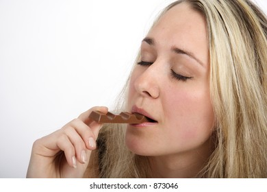 Portrait of a beautiful blond woman eating a bar of chocolate