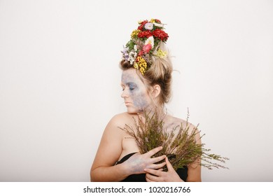 Portrait of a beautiful blond woman with flowers on her head, on a white background with colored flowers. Studio fashion photo of beautiful young woman with flowers in her  hair. Valentines day. Sprin