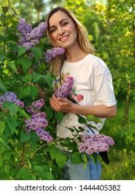 Portrait of beautiful blond woman near lilac outdoor