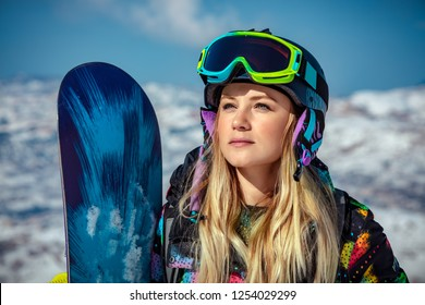 Portrait of a beautiful blond woman with snowboard standing in the snowy mountains, sportive wintertime activity