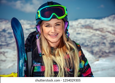 Portrait of a beautiful blond woman with snowboard in hand standing in the snowy mountains, sportive wintertime activity