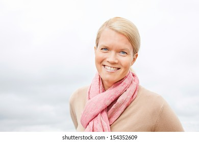 Portrait of a beautiful blond woman wearing a pink scarf