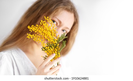 Portrait of beautiful blond woman in white dress holding yellow flowers of mimosa in her hand smiling and sniffing them on white background.