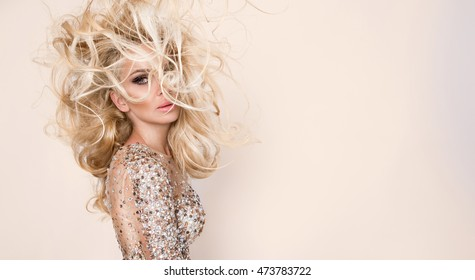 Portrait of the beautiful blonde with amazing hair and  eyes, dense long hair with highlights, green eyes and sensory perfect face dressed in sexy transparent dress with crystals