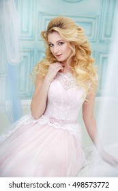 Portrait of a beautiful blonde bride with elegant curls in the interior.