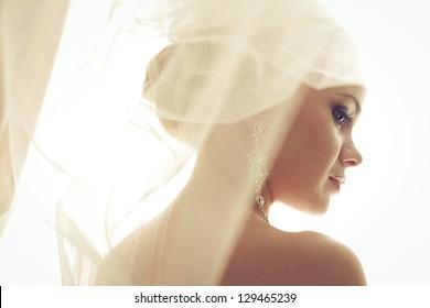 Portrait of a beautiful blonde bride. Wedding day. Daylight. Indoor shot