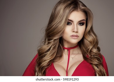 Portrait of beautiful blonde caucasian woman with long wavy hair and glamour makeup.