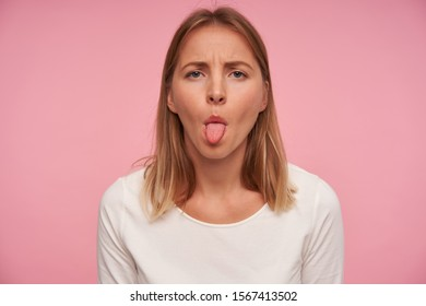 Portrait of beautiful blonde female with casual hairstyle frowning eyebrowns and showing her tongue while posing over pink background, wearing white blouse