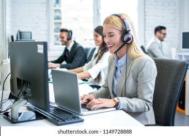 Portrait of beautiful blonde female customer service executive with headset using laptop in office