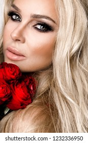 Portrait of a beautiful blonde female model with long, beautiful hair. Model in sexy lingerie, holding red roses.
