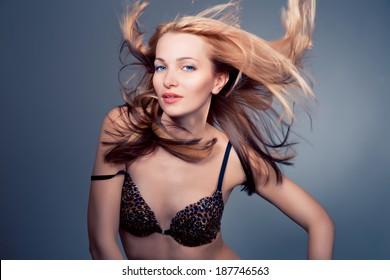 Portrait of a beautiful  blonde female model on blue background , Model wearing only leopard bra