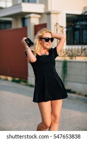 Portrait of beautiful blonde girl in black glasses and black dress comes with handbag.Hard light.