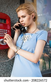 Portrait of beautiful blonde girl in blue dress talking on the payphone outdoors