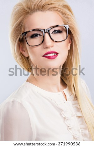 4c1316f8822 A portrait of beautiful blonde girl with blue eyes and red lips wearing  white blouse and glasses