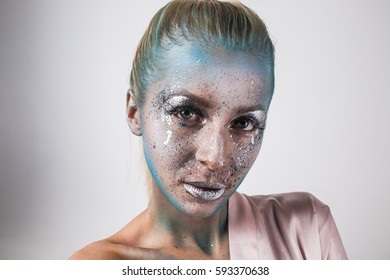 Portrait of beautiful blonde girl with fantasy bodyart makeup blue face art silver lips fashion isolated in studio