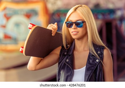 Portrait of beautiful blonde girl in glasses holding her skateboard on her shoulder while standing in skate park