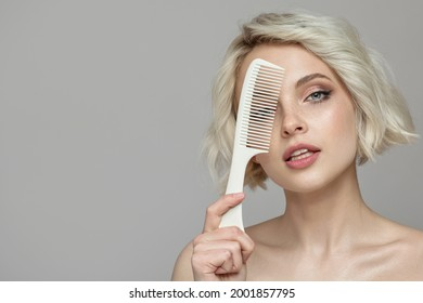 Portrait of a beautiful blonde girl holding a comb in her hand. Gray background.