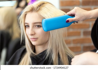 Portrait of a beautiful blonde girl in the interior of a beauty salon. The master hairdresser makes styling with a curling iron after successful dyeing of straight hair. Beautiful woman is smiling.