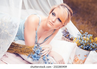 Portrait of beautiful blonde girl ,laying at summer green park under the canopy. tint