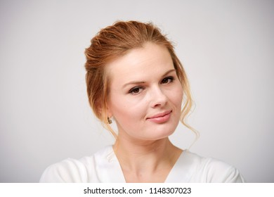 portrait of a beautiful blonde girl on a white background with a beautiful hairdress. She is right in front of the camera smiling and looking happy