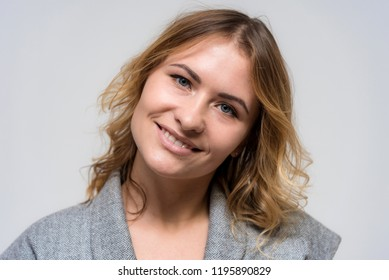 Portrait of a beautiful blonde girl on a white background in a dress. She is standing right in front of the camera, smiling and looking happy.